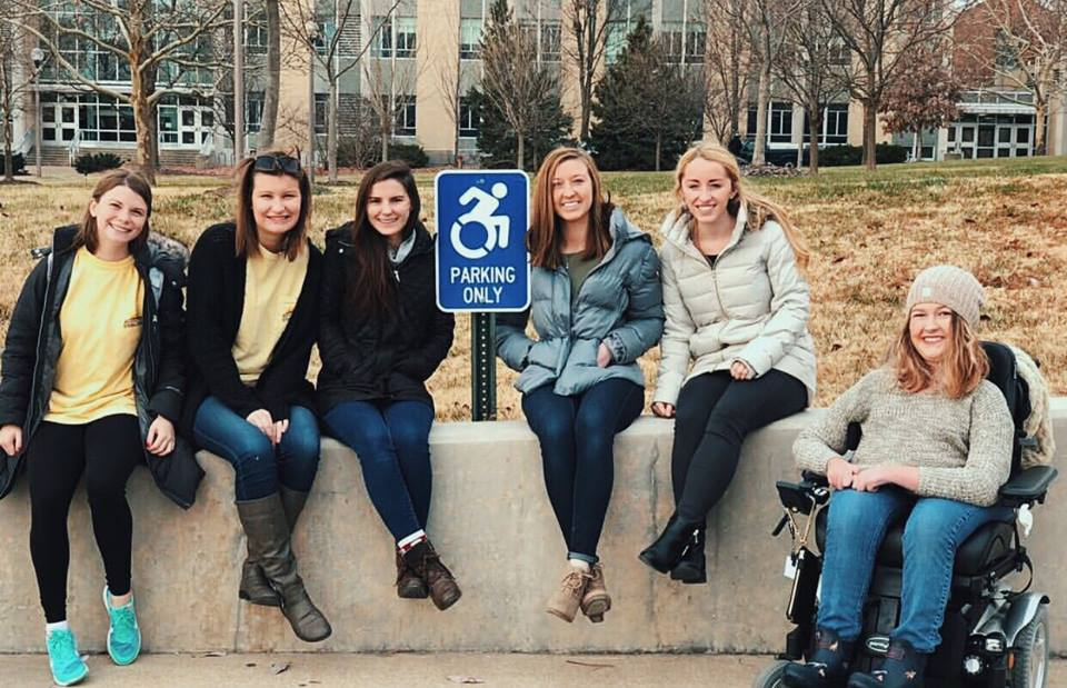 Students who funded new accessible parking signage pose with a new installation