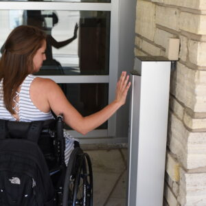 Kathleen using the accessibility button on the door at the Student Center