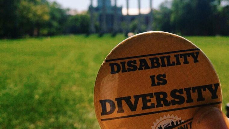 Disability is Diversity button is held up on the Quad with the Columns and Jesse Hall in the background
