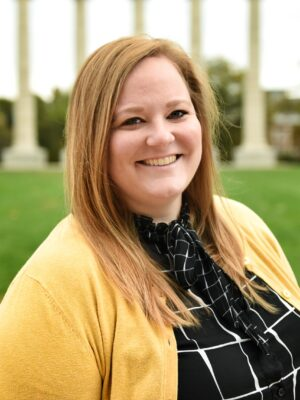 Headshot of Amber Lammers in a gold cardigan and black windowpane shirt.