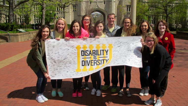 Students pose with the Disability is Diversity banner covered in signatures