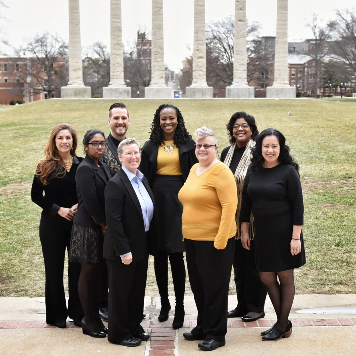 Eight-person staff on the Quad with the Columns in the background.