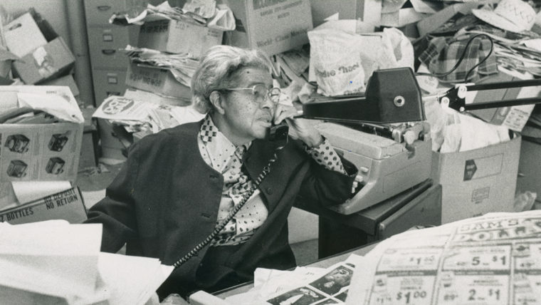 Lucile Bluford in her newsroom surrounded by paperwork