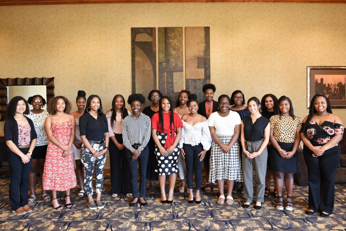 Large group shot of WOCHA 2019-20 participants in the lobby of the Hampton Inn. Patterned carpet and gold walls with art behind them. Two arcs including the students.