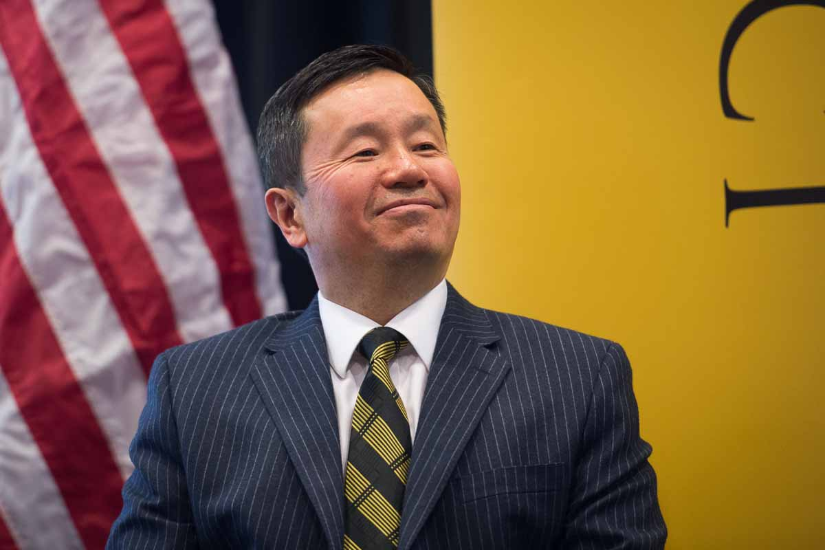 UM System Mun Choi photo in front of a gold background with an American flag beside him