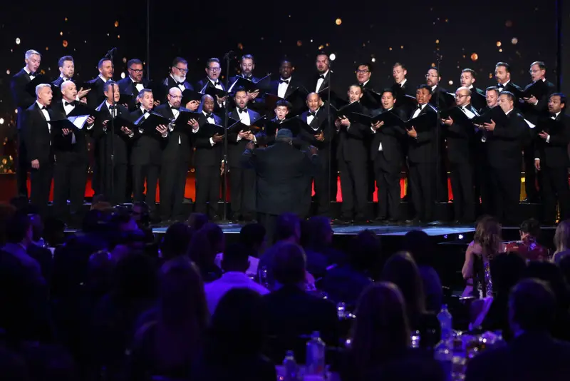 GMCLA in black tuxes on stage at the awards show.