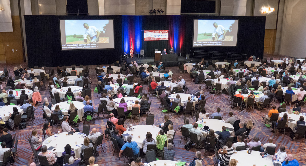 The Great Plains ADA Symposium takes place with people surrounding circular tables and two large projection screens