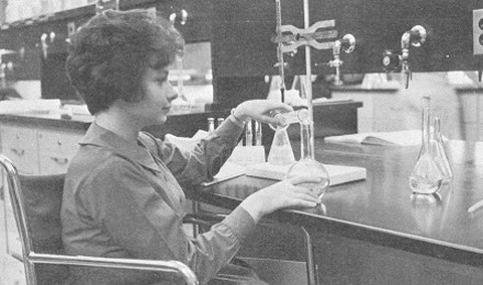 Woman in a wheelchair performing scientific research with beakers and flaks.