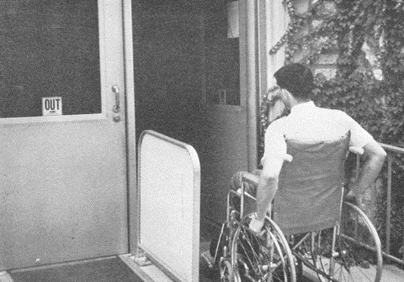 Man in a wheelchair using a ramp to enter a building.