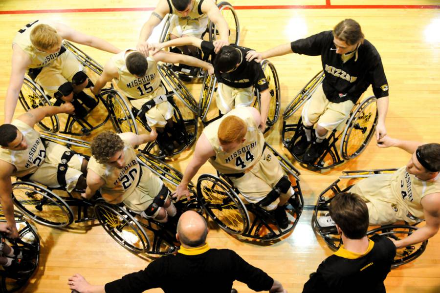Overhead photo of the Mizzou Wheelchair Baksetball team wearing gold uniforms and black shirts.