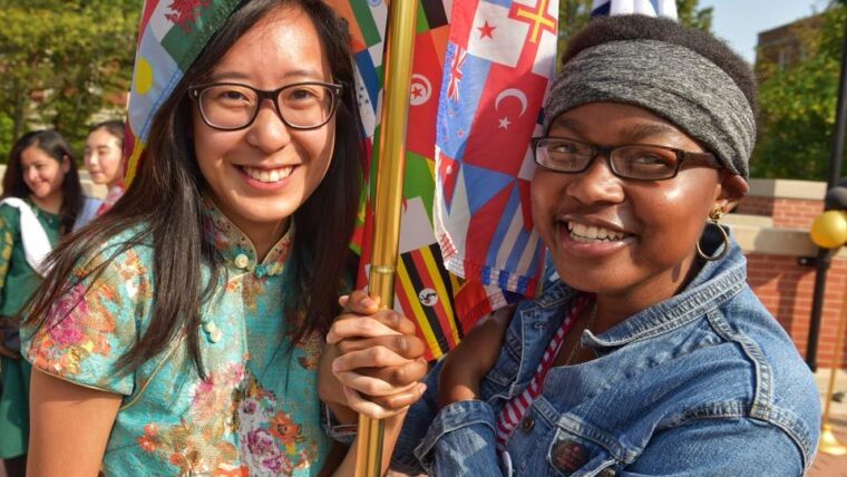 Two girls holding world flags with hands interlocked around the pole.