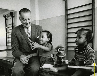 Dr. Rusk sitting on a table with two children and a toy by his side.