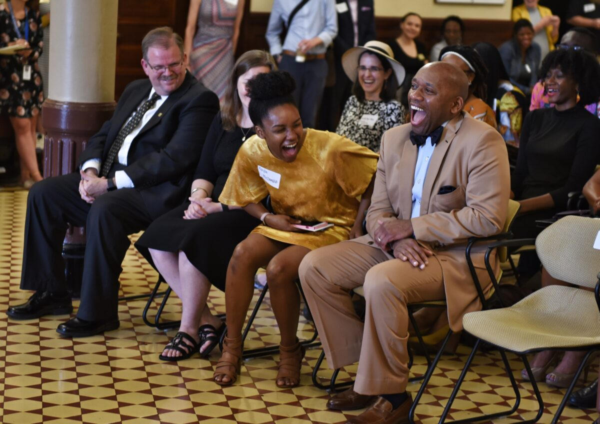 Kevin McDonald laughs with his daughter as Chancellor Alexander Cartwright looks on.