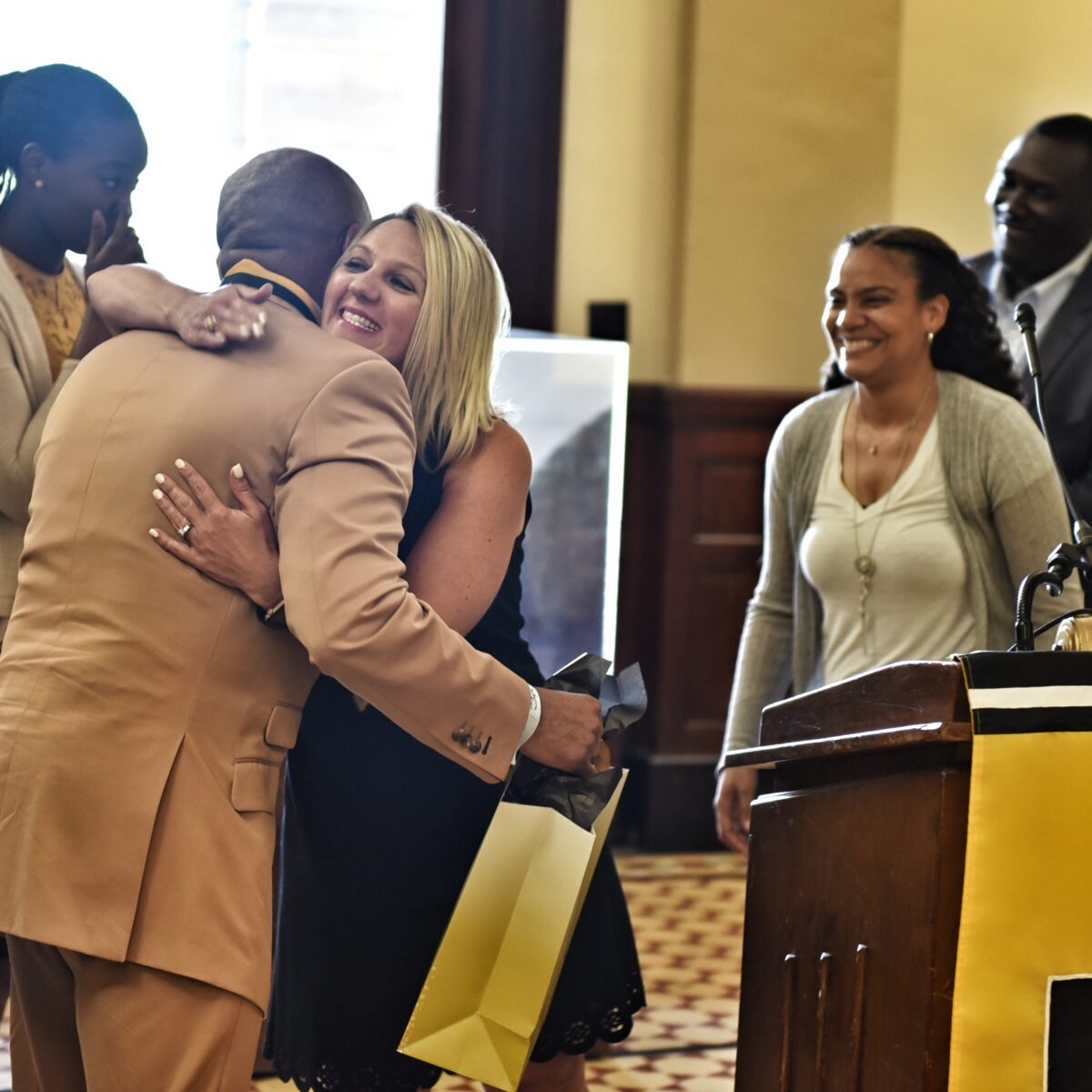 Andy Hayes, Assistant Vice Chancellor for Civil Rights, Title IX & ADA hugs McDonald as he accepts the gift.