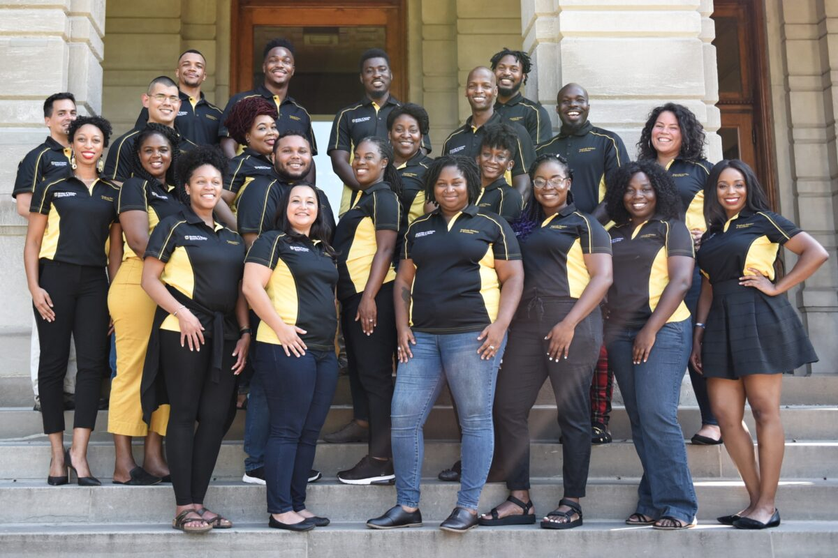 Group photo of GSE on the steps of Jesse Hall. GSE wearing black polos with gold panels on the sides.