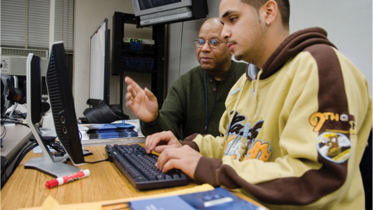 Student in a hoodie working at a computer with a mentor at his side.