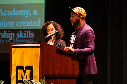 Dr. Terrell Morton wearing a blazer and ball hat with the brim up announcing results from the inaugural teach-in at a lectern with a gold MU banner on it..