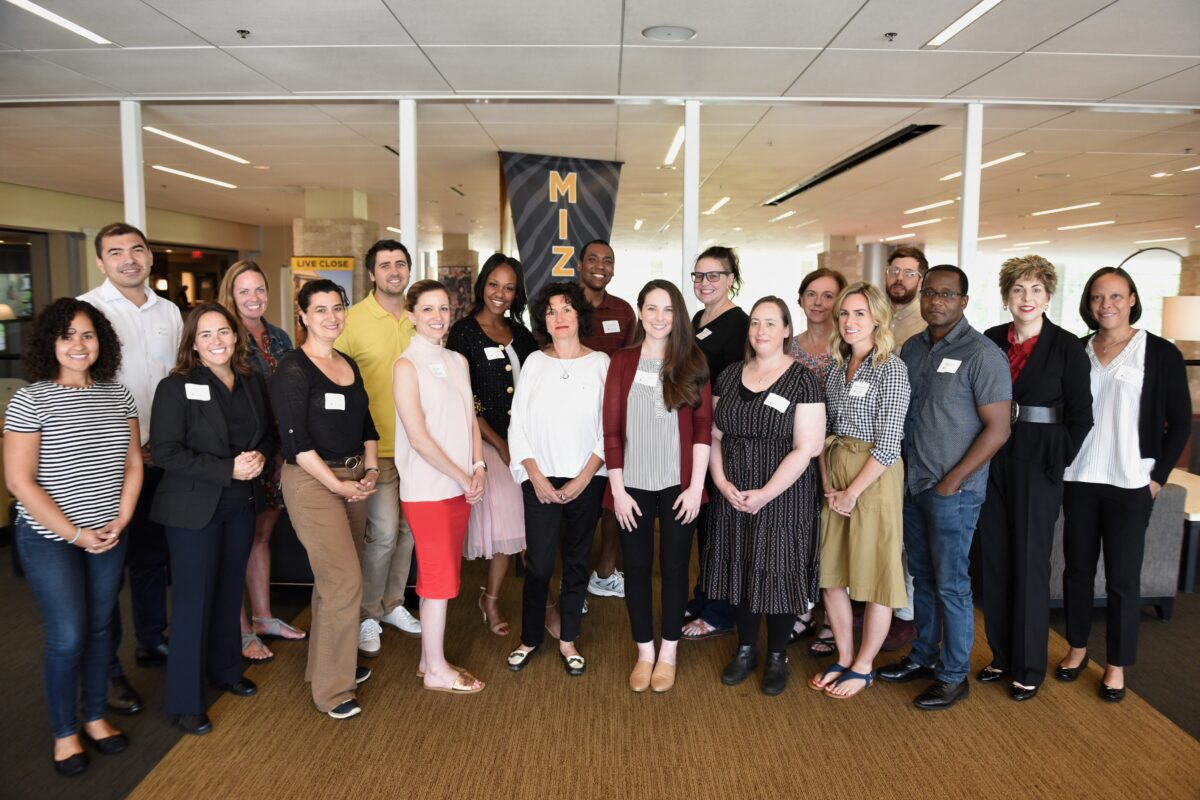 FIIT 2019-20 cohort standing on the sky bridge in the MU Student Center. Photo with lots of natural light, MIZ pennant hanging in the background.