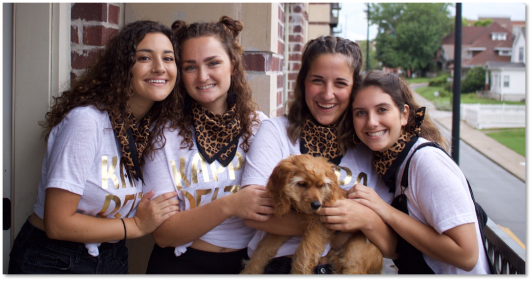 Emily and friends posing in matching handkerchiefs. They are holding a puppy and are wearing Greek letters.