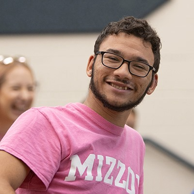 Headshot of Colby in a pink Mizzou shirt with white text on it.