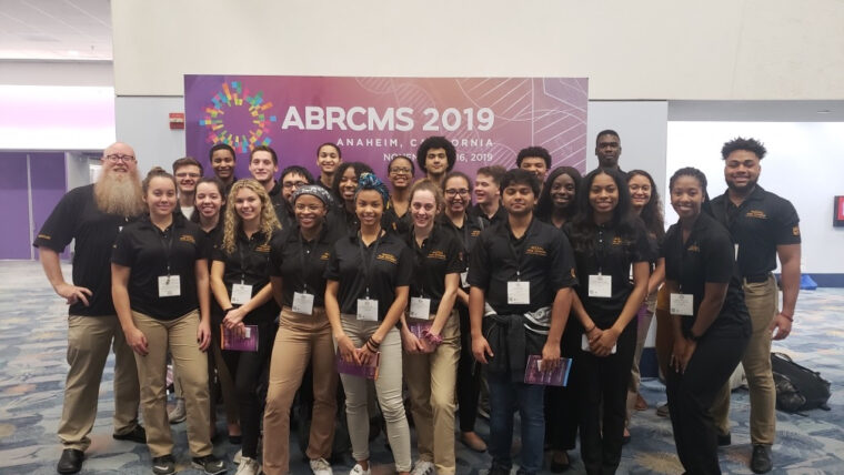 Large group of MU students and Booton in black polos in front of the ABRCMS 2019 poster.