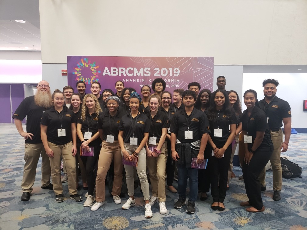Large group of MU students in black polos in front of the ABRCMS 2019 purple poster.