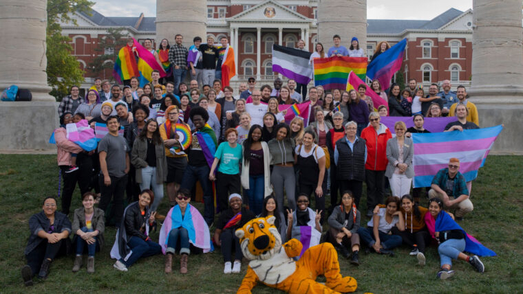 2019 Coming Out Week photo with lots of Mizzou and rainbow gear worn by participants. Picture on the Quad in front of the Columns.
