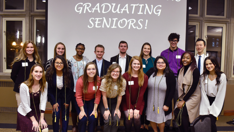 """Group photo of the banquet attendees in front of a screen reading """"Congratulations Graduation Seniors!"""""""