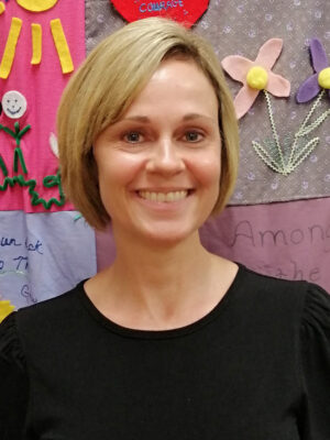 Headshot of Lisa Crader in a black shirt in front of the RSVP quilt