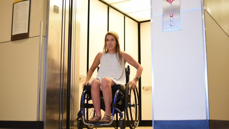 Woman using a wheelchair exiting an elevator