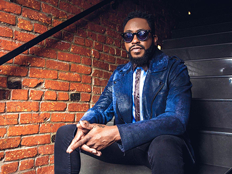 Posed photo of Raheem DeVaughn in a blue suit coat and sunglasses with a brick background