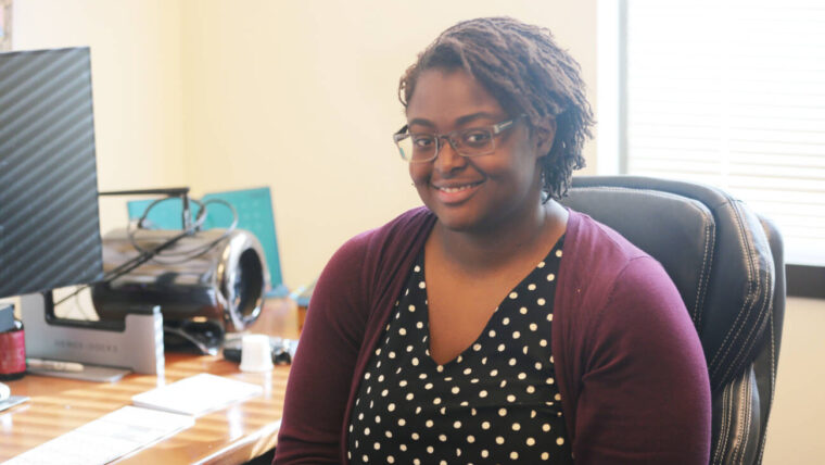 Photo of Samniqueka Halsey in her office in a black polka dot shirt with purple cardigan