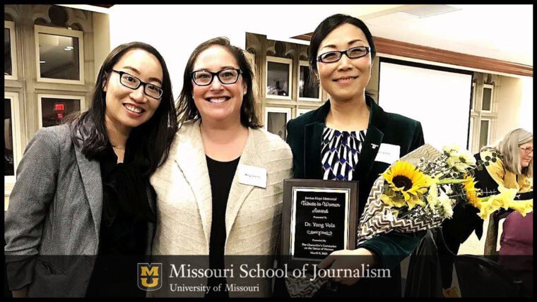 Grad student Lei Guo, professor Amy Simons and Asst. Prof. Yong Volz with the award placque and yellow flowers