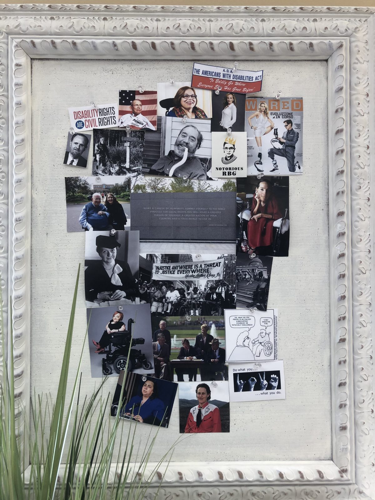 Cork board of disability rights movement iconography and images that hangs in Amber Cheek's office
