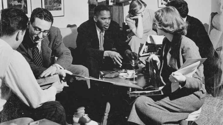 Black and white photo of Ridgel talks with students in a room during his time at MU.