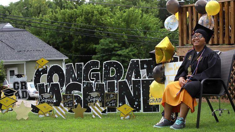 Jasmine-Kay sitting in her front yard in graduation regalia with balloons and a Congratulations yard sign